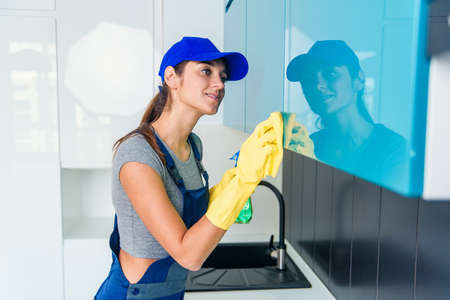 Cute young woman in workwear and protective rubber yellow gloves cleaning the furniture in modern hi-tech kitchen. Stockfoto