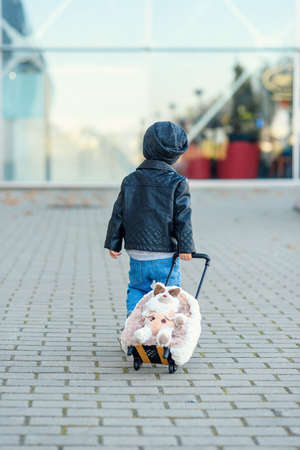 Cute little traveler girl pulls pink suitcase towards the airport. Stockfoto