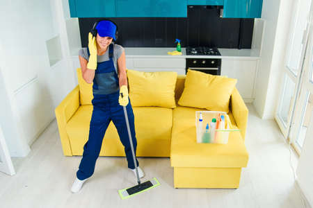 Caucasian woman as a professional cleaner in headphones cleaning floor with mop and listens to music at home. Stockfoto
