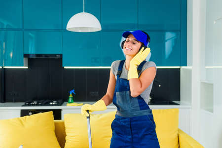 Attractive female worker listens to music with white headphones and dancing with the mop in contemporary stylish kitchen. Stockfoto