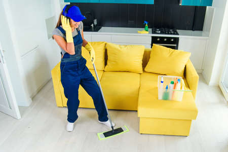 Beautiful female professional cleaner in special uniform with headphones washing the floor with mop and listens to music at apartment. Housework and housekeeping concept. Stockfoto