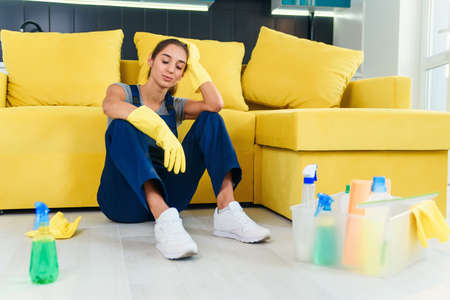 Young female worker of the cleaning service sitting near the couch and feeling tired after washing floor on cuisine.