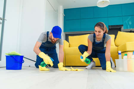 Smiling girl and handsome bearded man in workwears washing the parquet with the cleaning items and wipping with rags Stockfoto