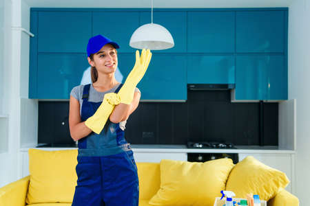 Cheerful girl in special working clothes wearing yellow rubber gloves and preparing to clean the cuisine in apartment.