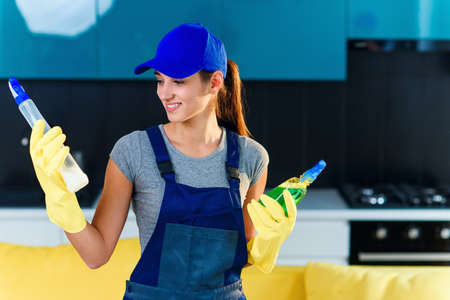 Positive female worker of professional cleaning service makes a choice between different cleaning agents on the background of modern cuisine. House cleaning service concept. Stockfoto