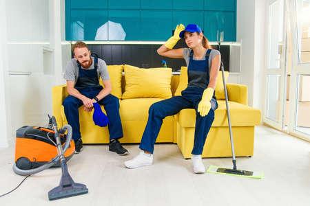 Felice coppia di addetti alle pulizie professionali che riposano nel divano dopo aver pulito la cucina. Archivio Fotografico