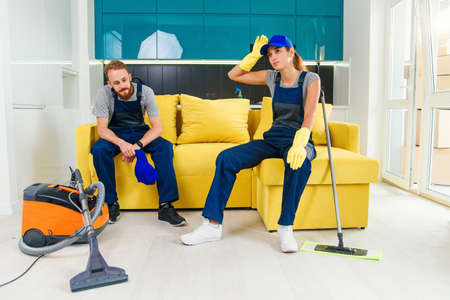 Happy couple of professional cleaners having rest in sofa after cleaning cuisine. Reklamní fotografie