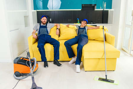 Happy couple of professional cleaners having rest in sofa after cleaning cuisine. Stockfoto