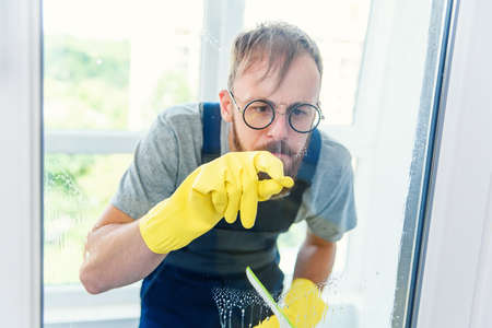 Cheerful bearded man in funny eyeglasses cleans the window with detergents and remove dirt with his finger in gloves. Stockfoto