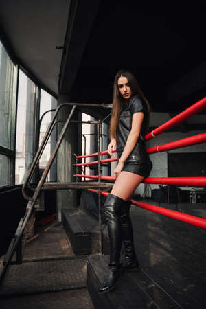 Attractive model wearing leather shorts and jacket posing on boxing ring. Stockfoto