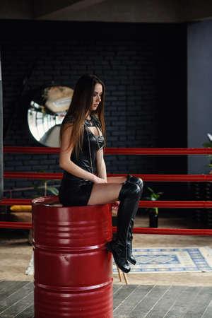 Hermosa chica en ropa de cuero se sienta en barril rojo en el centro del ring de boxeo. Foto de archivo