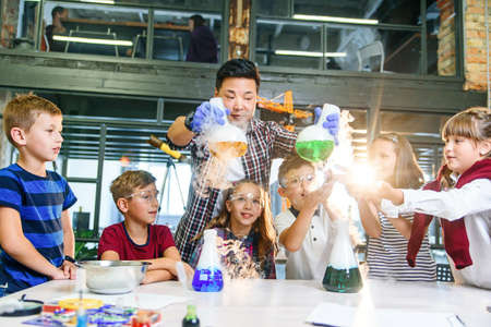 Asian young teacher with group of six cheerful caucasian 8-10 years pupils wearing protective glasses during chemical experiment with colored liquids in modern school.