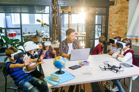 Korean teacher with six caucasian pupils using augmented reality VR Glasses in a computer science elementary classroom. Knowledge for future, science new technology and people concept.