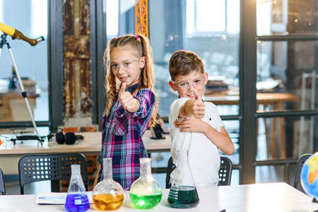 Portrait shot of two cheerful Caucasian scientist kids in safety goggles showing thumbs up in primary school chemical class. Science, chemistry and children. Slow motion Stockfoto