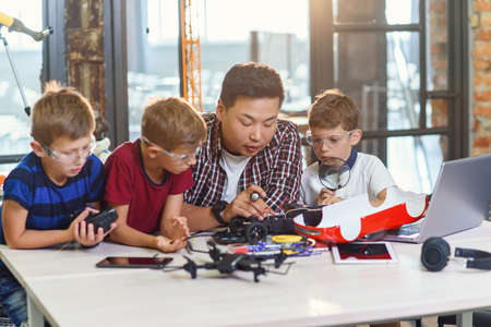 Young Korean man of electronics engineer with young children using screwdriver to disassemble robotic machine at the table in the modern school. Slow motion Stockfoto