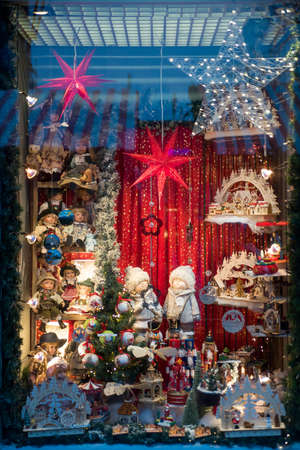 Stylish window store with christmas toys at holiday market in city street. Christmas street decor.