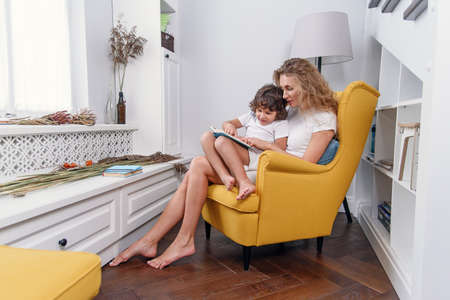 Beautiful mother reads child book to her little son while sitting in comfortable yellow chair near window at cozy home.