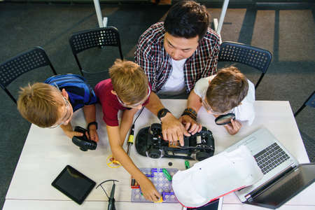 Electronics engineer teacher with young european students working together with a radio controlled car model. Soldering of wires and circuits, physical experiments. Stockfoto