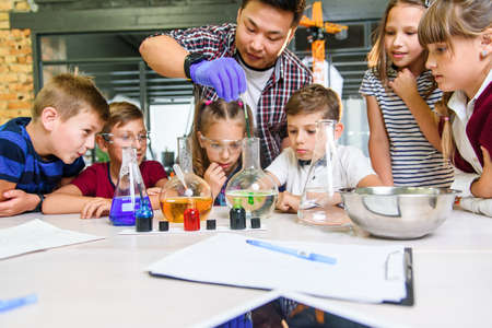 Korean scientist shows to primary school pupils chemical reaction experiments at modern lab class. Stockfoto