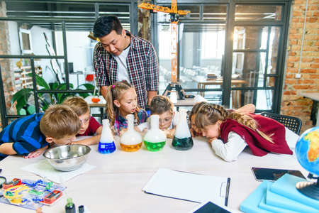 Caucasian school children in chemical lab. Pupils put dry ice into the flasks with colored liquids which causes intensive vaporization. Science, chemical reaction and educational concept. Stockfoto