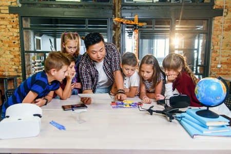 Six creative school children with young asian teacher study an electronic constructor with fan and turn on flashlight. Creative pupils with teacher working on the tech project at school.