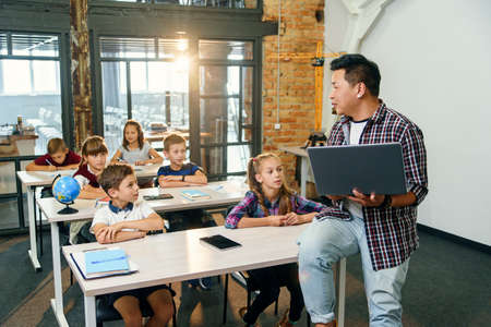 Asian male teacher sits on desk with laptop in hands and explaining lesson for six elementary school pupils. School Children sitting at desks listening their lecturer. Stockfoto