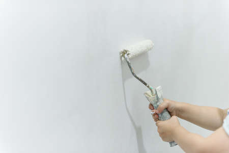 Painting out a white wall with a paint roller with white paint. Close up female hand painting wall with paint roller.