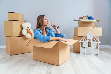 Happy woman drinks champagne from a glass while sitting inside a cardboard box in new apartment.