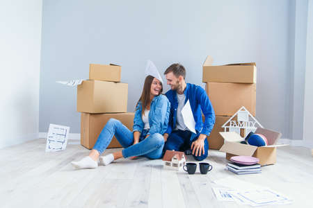 Happy cheerful couple in love having fun together in their own new flat after removing on the cardboard boxes background Imagens