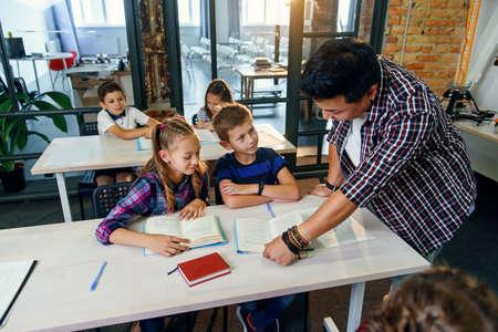 Male teacher explains lesson task for pupil in classroom. Stock fotó