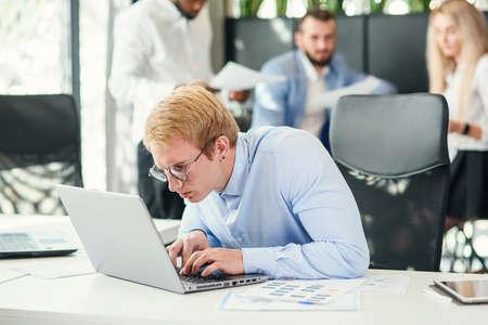 Ein fröhlicher, zielgerichteter männlicher Büroangestellter mit lustigen Brillen sitzt an seinem Arbeitsplatz und verwendet einen Laptop, um finanzielle Aufgaben zu lösen. Standard-Bild
