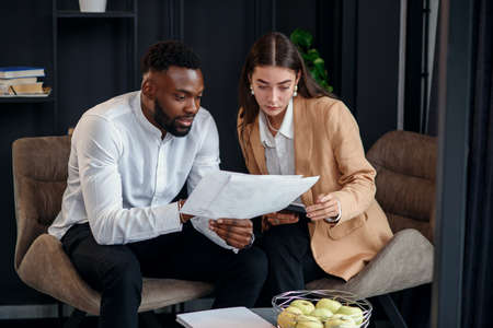 Business couple of african american man and european woman which sitting in specially designated room and using paper documents and tablet pc, conversing about their business project and their successful strategy.
