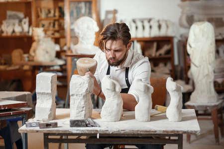 Männlicher Handwerker in Arbeitsuniform macht im Kreativstudio eine Kalksteinkopie des Frauentorsos und zeigt den Herstellungsprozess von Anfang bis Ende.
