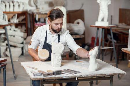 Male sculptor in white shirt and black apron makes a limestone copy of woman torso at the artistic studio.
