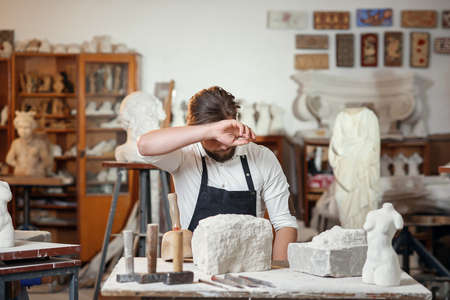 Male sculptor in white shirt and black apron makes a limestone copy of woman torso at the artistic studio. Banque d'images