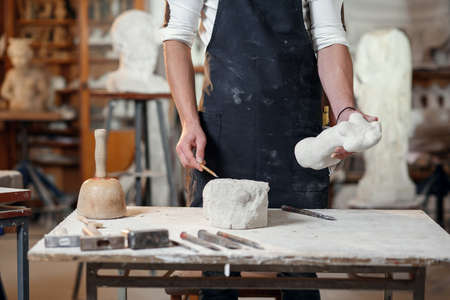 Close up craftsman hands working with stone sculptor at creative workplace in the atmospheric studio.
