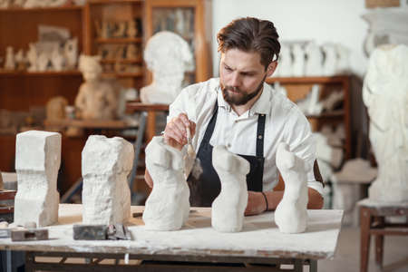 Stonemason which sitting in creative workshop and scraping the remains of lime-stone using brush