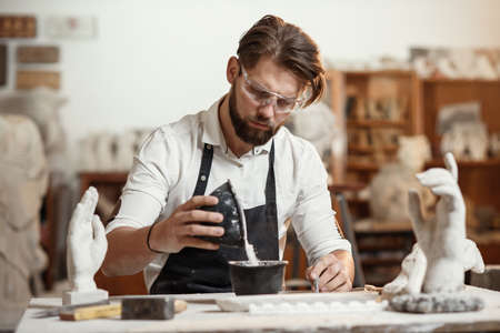 Unrecognizable professional stonemason with well-maintained hands making glue in special vessel for his handmade sculpture