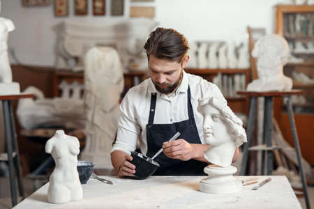 Skillful sculptor makes professional restauration of gypsum sculpture of womans head at the creative workshop.