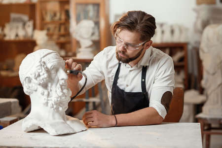 Male sculptor repairing gypsum sculpture of womans head at the working place in the creative artistic studio.