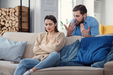 Offended angry woman sits on sofa at home after an argument with her husband. Broken marriage.