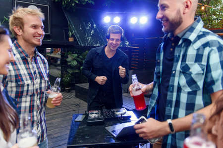 Caucasian people dancing and drinking low alcohol drink and having fun together on birthday party celebration while DJ works with mixing console. Stock Photo