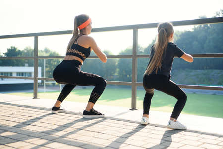 Sporty beautiful slender elder and younger sisters which squating together during fitness training outdoors.