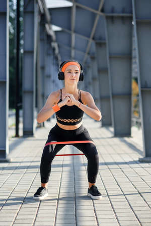 Slow motion of resistance band fitness girl in earphones which doing squat exercises with fabric booty band during her sport workout on special sportground