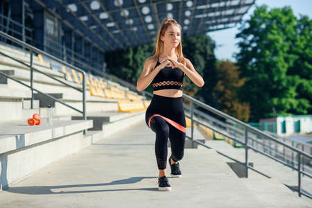 Young sporty woman doing exercises with rubber band outdoor
