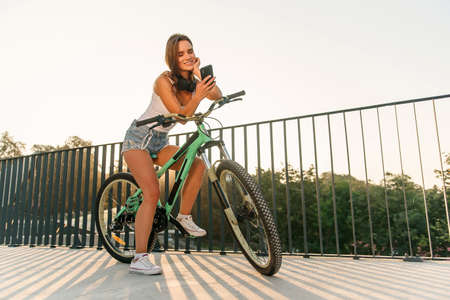 Attractive girl sits on bicycle and using smartphone at sunrise on cityscape background.