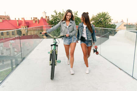 Portrait of two young attractive urban women walking with a bike and skateboarding on the street in sunny summer day. Slow motion.