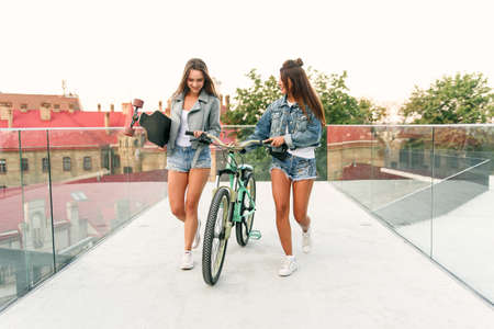 Gorgeous joyful 30s women in stylish jackets and enticing shorts going with bicycle and skateboard in specially equipped place with glass walls