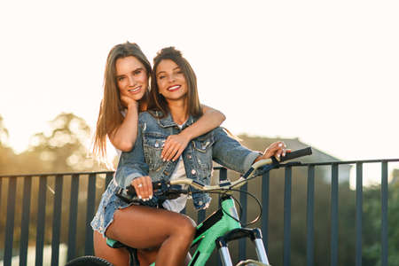 Gorgeous cheerful young woman hugging her charming female friend sitting on the bicycle and looking at camera with nice smiles on the sundown background