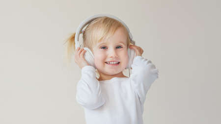 home, technology and music concept - little girl with headphones listening to music and singing